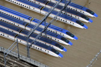 Bullet trains sit submerged in muddy waters in Nagano, central Japan on Sunday.