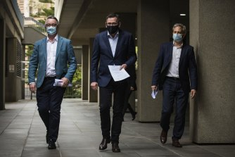 Victorian Health Minister Martin Foley, Victorian Premier Daniel Andrews and Victorian Chief Medical Officer Brett Sutton arrive at the daily press conference on Sunday.