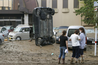 A car stands vertically on a muddy road after being washed away by flood, in Hitoyoshi, Kumamoto prefecture.
