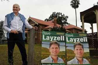 Former Nationals MP George Souris stands outside his home with a poster for current candidate David Layzell.