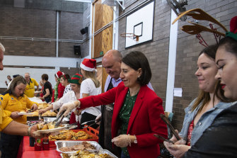 Premier Gladys Berejiklian and Emergency Services Minister David Elliott serve Christmas lunch to firefighters at Colo Heights.