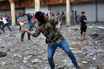 An anti-government protester prepares to throw a molotov cocktail during clashes in Baghdad last week.