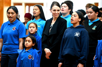 New Zealand Prime Minister Jacinda Ardern stands with students from Te Wharekura o Manurewa school as they perform ahead of receiving her first COVID-19 Pfizer dose on Friday.