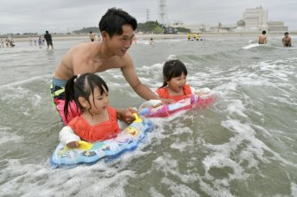 A family plays in the water at Kitaizumi Kaisui beach in Minamisoma, Fukushima Prefecture, after the beach opened to the public for the first time since 2011.
