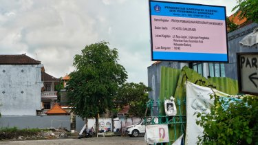 A building permit sign for a 700-sqm building on the 800-sqm site was placed above fading photos of the bombing victims at the former Sari Club site in Bali on Wednesday.