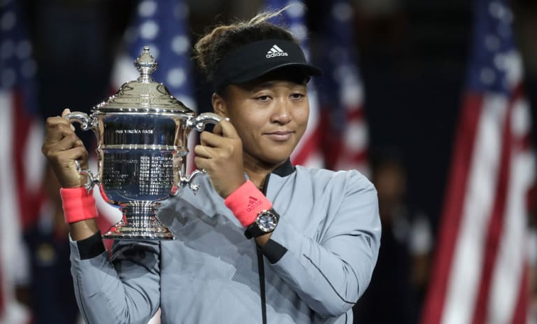 Naomi Osaka, the first Japanese-born winner of a grand slam, holds the US Open trophy after beating Serena Williams.