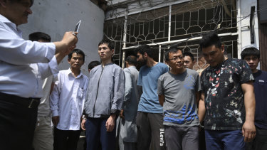 A Pakistani official takes pictures of Chinese nationals detained on trafficking charges.