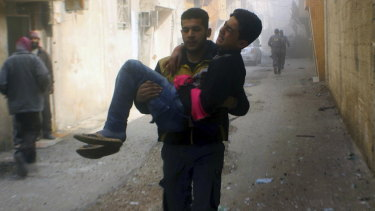 Members of the Syrian Civil Defence group carrying a young man who was wounded during airstrikes and shelling by Syrian government forces, in Ghouta, a suburb of Damascus, Syria.