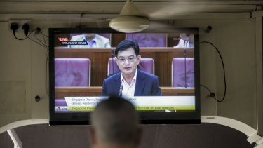 A man watches a television showing Singapore's Deputy Prime Minister Heng Swee Keat annoucing a major new economic stimulus package.