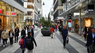 Pedestrians walking pass shops on Drottninggatan in Stockholm, Sweden, on Monday.