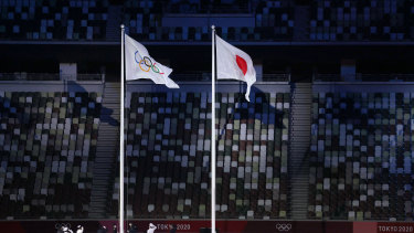 The Olympic flag is raised alongside the Japanese flag.
