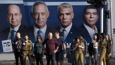 People wait for a green light next to an election campaign billboard showing Blue and White party leaders, from left, Moshe Yaalon, Benny Gantz, Yair Lapid and Gabi Ashkenazi in Ramat Gan, Israel, on Sunday.