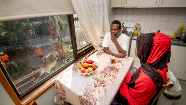 Tooyo Cabdi and his daughter Naima sit in the kitchen of their apartment, as a drilling rig works away outside.