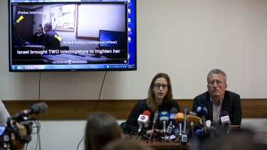 Palestinian Bassem Tamimi, right, sits during a press conference while a video of his daughter's interrogation plays on the screen.