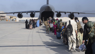 A US Air Force on loads people being evacuated from Afghanistan onto a C-17.