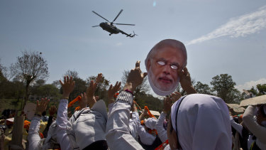 A supporter of India's ruling Bharatiya Janata Party (BJP) holds a face mask of Indian Prime Minister Narendra Modi.