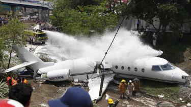 A fire truck sprays foam on the jet that appears broken in half near the centre.