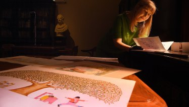 NSW State Library curator Sarah Morley inspects illustrations by children's author and illustrator Pamela Allen.