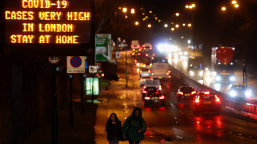 As a new strain takes hold in Britain, a sign near a highway in London urges people to stay at home.