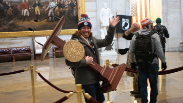 A pro-Trump protester identified as Adam Johnson carries the lectern of Speaker of the House Nancy Pelosi through the US Capitol Rotunda.