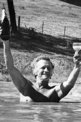 Clifton Pugh celebrates his Archibald Prize win with champagne in the dam at his Cottlesbridge home