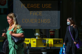 """A woman wearing a protective face mask passes a sign reading """"Please Use Face Coverings"""" in the financial district in the City of London."""
