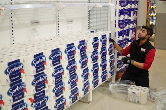 Workers restock shelves at one of Coles' supermarkets on Thursday night.
