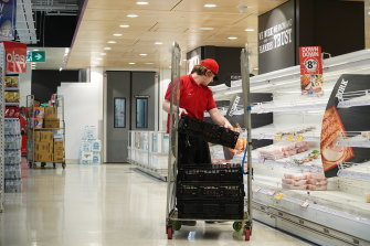 Restocking an empty fridge at a Coles supermarket.