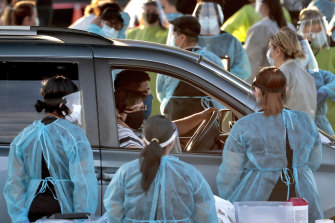 A family pulls up to a drive-through testing site in Phoenix, Arizona, where the virus is out of control.