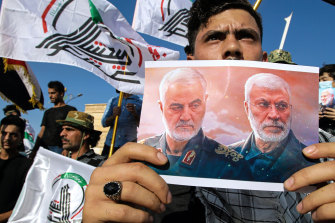 A supporter of an Iran-backed militia holds a poster of slain Iranian General Qassem Soleimani, left, and deputy commander Abu Mahdi al-Muhandis during a protest by pro-Iranian militiamen in Iraq.