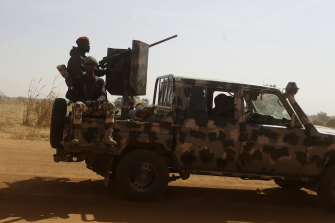 Nigerian soldiers drive past a secondary school in Kankara in December. Rebels have abducted hundreds of school children in several attacks in Nigeria.