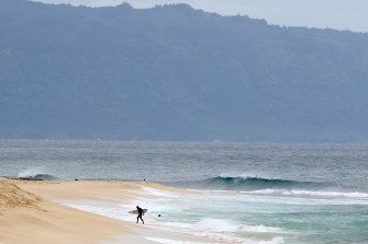 A surfer walks out of the ocean on Oahu's North Shore near Haleiwa, Hawaii.