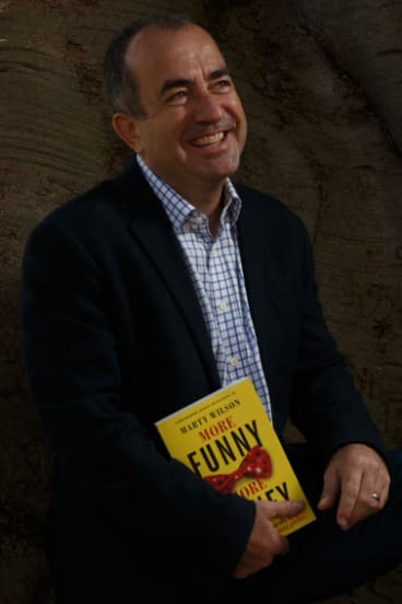 Comedian and author Marty Wilson with his book, More Funny More Money.