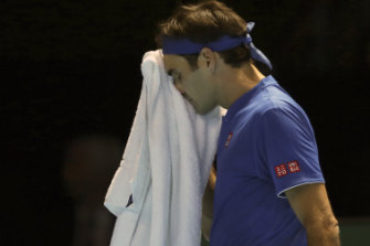 Toweled up: Roger Federer wipes his face during his straight sets loss to Kei Nishikori.