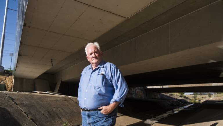 Electrical Trades Union officer Mick Koppie stands under two sets of cable trunking – enclosures used to protect electrical cables - installed beneath a bridge on Flemington Road.