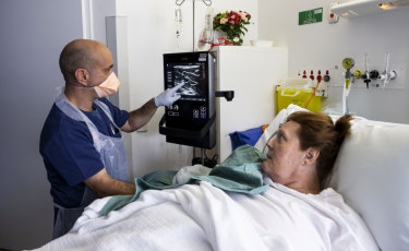 Dr Evan Alexandrou uses ultrasound technology to find a vein on patient Cheryl Tate at Liverpool Hospital.
