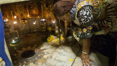 A Christian worshipper prays at the Grotto, under the Church of the Nativity.