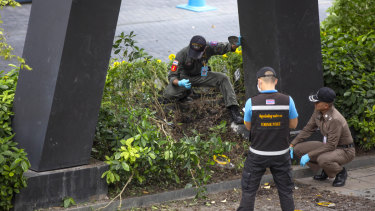 Thai investigators examine a site of an explosion that injured people in Bangkok on Friday.