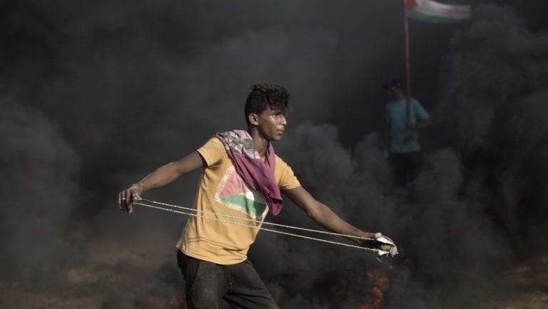 A Palestinian protester hurls stones at Israeli troops during a protest at the Gaza Strip's border with Israel on Friday.