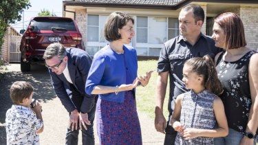 Premier Gladys Berejiklian talks solar power to Casula residents Adam and Leanne Gaudry with daughter Mia, 8, while Treasurer Dominic Perrottet chats to son Liam, 4.