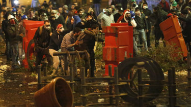 Anti-government protesters clash with riot police near Parliament square in downtown Beirut on Sunday.
