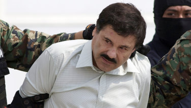 "Joaquin ""El Chapo"" Guzman, the head of Mexico's Sinaloa Cartel, is escorted by police following his 2014 capture in the beach resort town of Mazatlan."