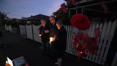 Vietnam veteran Rod Coote, son Nathan and wife Julie observe a live stream of ANZAC day's dawn service outside their house in Melbourne.