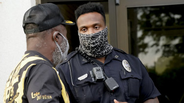 A citizen speaks with an officer in front of the municipal building after a deputy shot and killed a black man while executing a search warrant in North Carolina on Thursday (AEST).