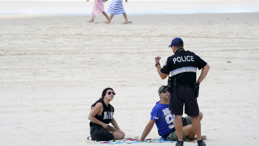 A police officer speaks with sunbathers on a Gold Coast beach in April.