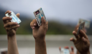 Migrants hold up their Honduran national ID cards as Guatemalan police block their passage at the Honduras-Guatemala border.