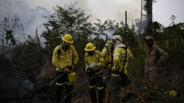 Firefighters rest briefly as they put out fires along the road to Jacunda National Forest.