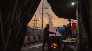 Farmers prepare dinner on a blocked highway outside New Delhi in protest against new farm laws.