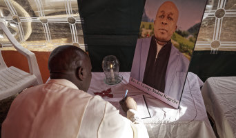 Father Michael Wa Mugi lights a candle and signs the book of condolence next to a photo of Catholic priest Reverend George Mukua Kageche, who died in the Ethiopian Airlines plane crash.