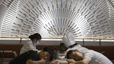 Restaurant workers nap on tables at a restaurant in a shopping centre in Beijing.